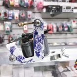 Photo of a white and purple floral pattern tattoo machine.
