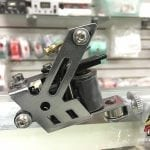 Photo of a chrome v-shaped tattoo machine.